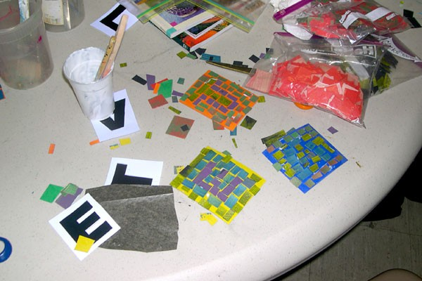 Colored papers are assembled to make mosaics.